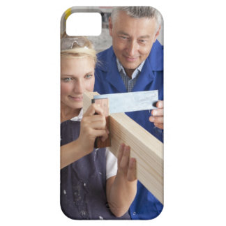 Teacher helping student measuring planed wood in iPhone SE/5/5s case