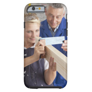 Teacher helping student measuring planed wood in iPhone 6 case