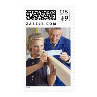 Teacher helping student measuring planed wood in postage stamp