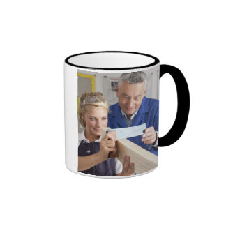 Teacher helping student measuring planed wood in ringer coffee mug