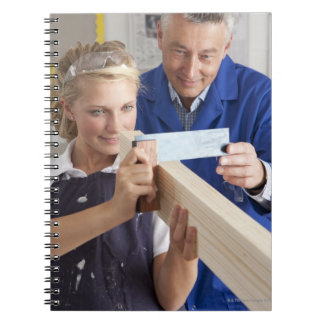 Teacher helping student measuring planed wood in spiral notebook