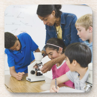 Teacher helping students use microscope in coaster