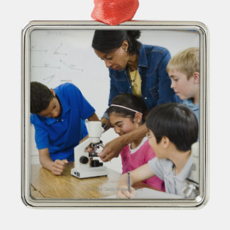 Teacher helping students use microscope in metal ornament