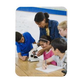 Teacher helping students use microscope in rectangular photo magnet