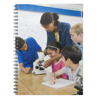Teacher helping students use microscope in spiral notebook