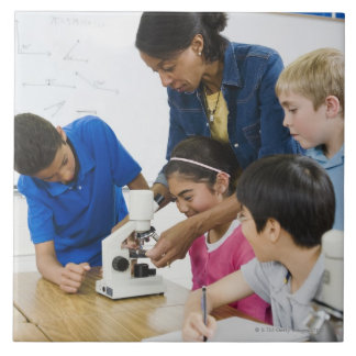 Teacher helping students use microscope in tile