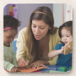 Teacher helping toddlers color at daycare beverage coasters