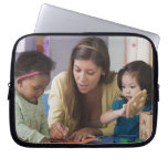 Teacher helping toddlers color at daycare laptop sleeve