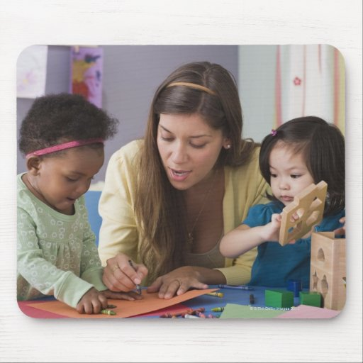 Teacher helping toddlers color at daycare mousepad