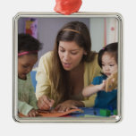 Teacher helping toddlers color at daycare ornaments