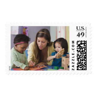 Teacher helping toddlers color at daycare postage stamps