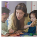 Teacher helping toddlers color at daycare large square tile