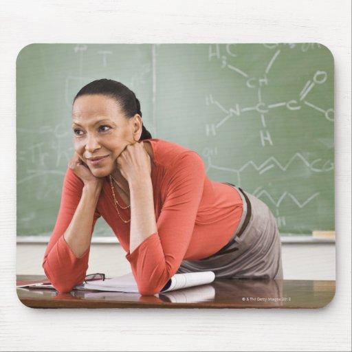 Teacher leaning on desk by chalkboard mousepad