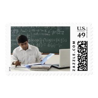 teacher sitting at desk, working stamps