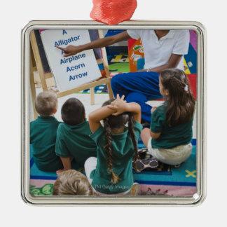 Teacher with preschool students in classroom metal ornament
