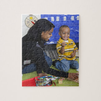 Teacher with toddler in daycare puzzles