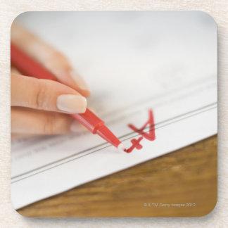 Teacher writing A plus grade on worksheet Beverage Coaster
