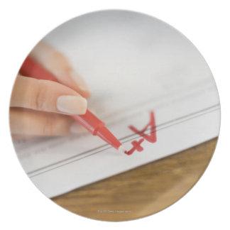 Teacher writing A plus grade on worksheet Plate