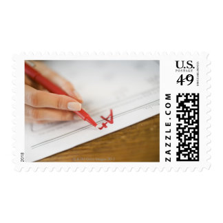 Teacher writing A plus grade on worksheet Postage