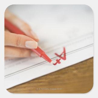 Teacher writing A plus grade on worksheet Square Sticker