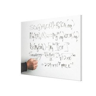 Teacher writing chemical formulae on white board canvas print