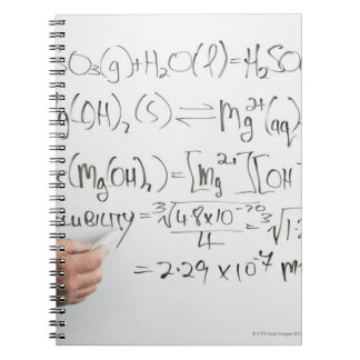 Teacher writing chemical formulae on white board spiral note book