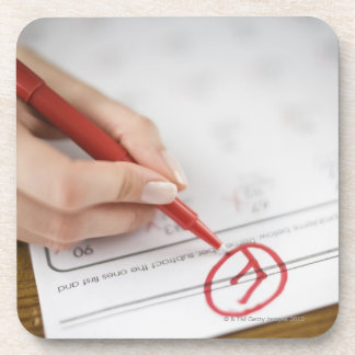Teacher writing F grade on worksheet Coasters