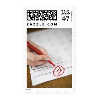 Teacher writing F grade on worksheet Postage Stamp