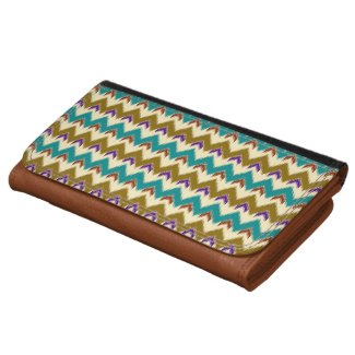 A purse with a native tribal pattern of feathered chevrons and arrows in teal, brown, red, blue and beige
