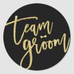 """Team Groom Bow Tie Bachelor Party Wedding Stickers<br><div class=""""desc"""">This design features a modern and bold gold 'team groom' brushed calligraphy script with a stylish bow tie accent on a classic black background. The background color can be changed to any color of your choice. You can easily add more text / info / details and/or photos to this product....</div>"""