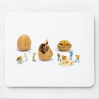 Team of miniature figurines transporting walnut mouse pad