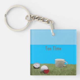 Tee time with golf ball and cup of tea on green keychain