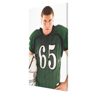 Teen football player holding helmet, portrait canvas print