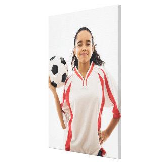 Teen girl holding soccer ball in hand, portrait canvas print