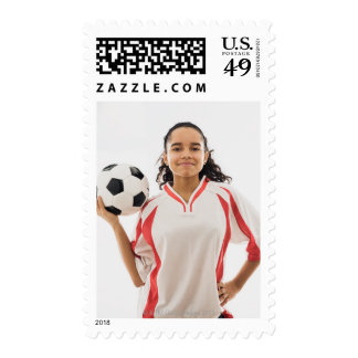 Teen girl holding soccer ball in hand, portrait postage
