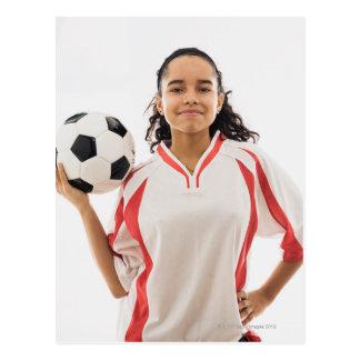 Teen girl holding soccer ball in hand, portrait postcard