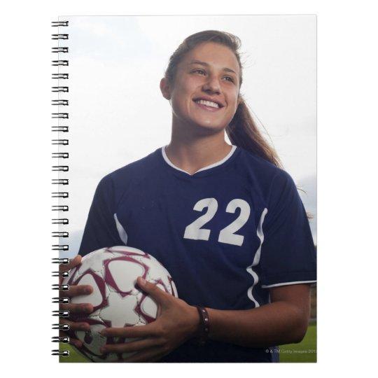 teen girl soccer player holding soccer ball notebook