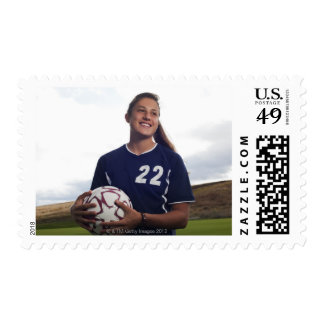 teen girl soccer player holding soccer ball postage