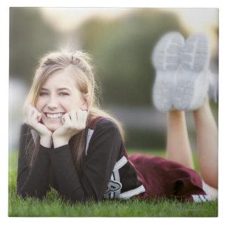 Teen relaxing on grass tile
