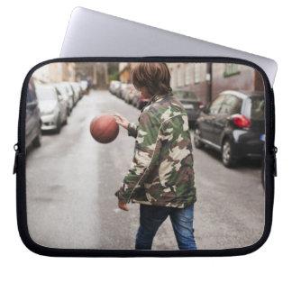 Teenage boy dribbling basketball computer sleeves