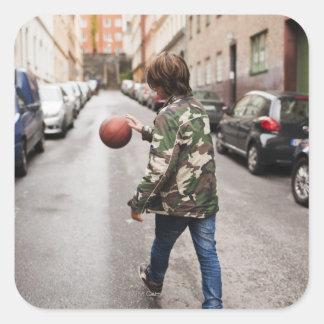 Teenage boy dribbling basketball sticker