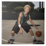 Teenage boy on basketball court large square tile