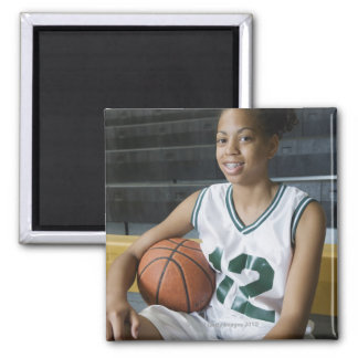Teenage girl (13-15) wearing basketball uniform, 2 inch square magnet