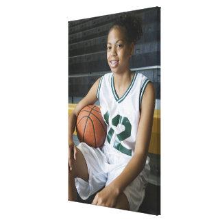Teenage girl (13-15) wearing basketball uniform, canvas print