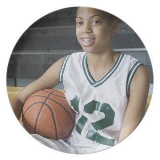 Teenage girl (13-15) wearing basketball uniform, dinner plate