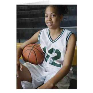 Teenage girl (13-15) wearing basketball uniform, greeting card