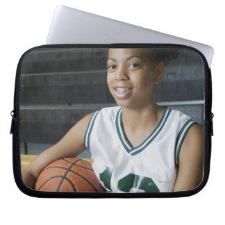 Teenage girl (13-15) wearing basketball uniform, laptop computer sleeve