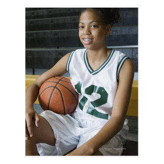 Teenage girl (13-15) wearing basketball uniform, postcard