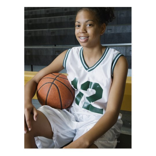 Teenage girl (13-15) wearing basketball uniform, postcard