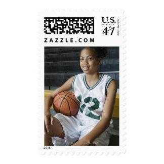 Teenage girl (13-15) wearing basketball uniform, stamp